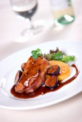 Cripsy skinned duck breast served with polenta, mesclun and a decadent port demi glace with figs.  Shallow dof.